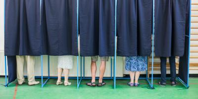 People in voting booths with only their feet visible beneath the curtains