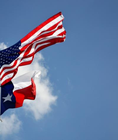 The flags of texas and the United States fly together