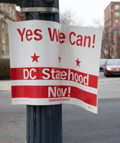 "A sign saying ""Yes we can! DC Statehood Now!"" hanging on a lamppost with traffic going by in the background."