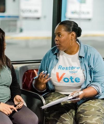 A person wearing a Restore Your Vote t-shirt talking to another person on a bench.