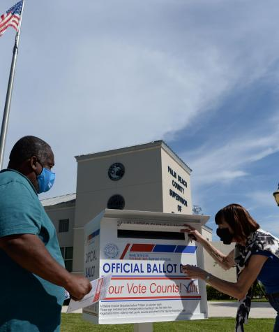 A man and woman submit their ballots into a drop box