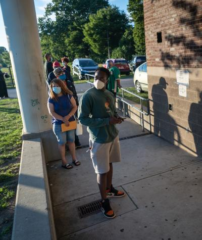 "Voters line up along a concrete ramp outside a propped open door with a ""Vote Here"" sign on it."