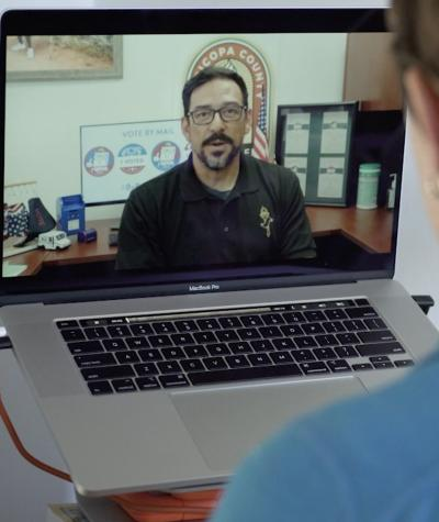 An over the shoulder shot of a person speaking to a man on a laptop screen