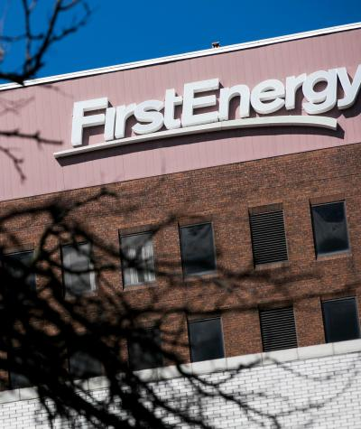 The FirstEnergy logo on the outside of a building with dark branches of a tree in the foreground.