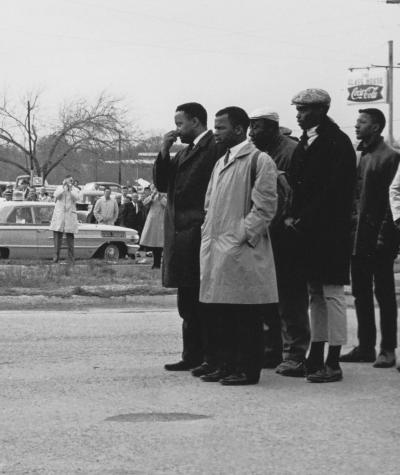 John Lewis and other protestors standing in a group on one side and state troopers walking towards them from the other side