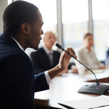 Man speaking into microphone at a meeting