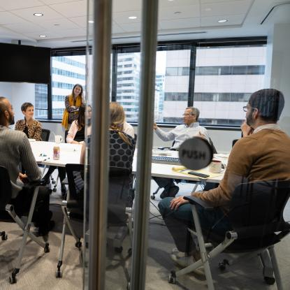 People sit around a table in a conference room seen through an open glass door