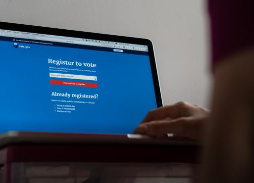 A close up of a laptop screen with a voter registration website and a person's hand on the keyboard