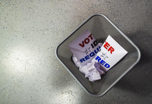 """Voter ID required"" sign in a trash can"