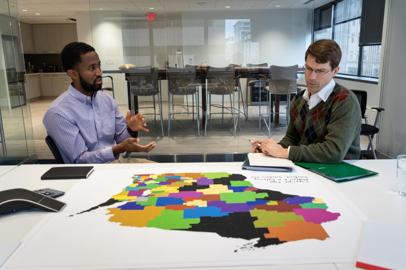 Two people sit at a conference table looking at a map of Wisconsin with district lines drawn.